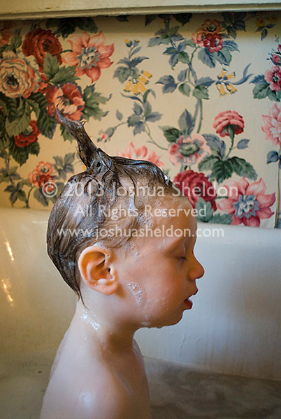 Baby boy in bathtub with hair up in a spike