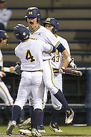 Michigan Wolverines catcher Dominic Jamett (41) celebrates with teammate Ako Thomas (4) after he scored in the bottom of the ninth inning against the Oakland Golden Grizzlies on May 17, 2016 at Ray Fisher Stadium in Ann Arbor, Michigan. Oakland defeated Michigan 6-5 in 10 innings. (Andrew Woolley/Four Seam Images)