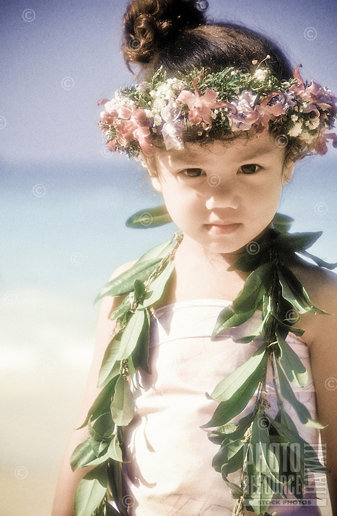 Young girl at the beach wearing a maile lei