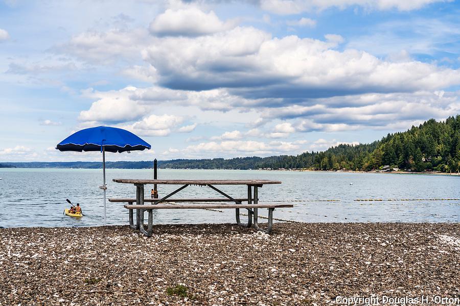Picnic table, kayakers and swimmers at Twanoh State Park, Washington, USA