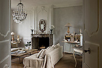 Contemporary sofas draped in natural hemp are combined with an antique crystal chandelier and a Gustavian bureau in the salon which has retained its original marble fireplace