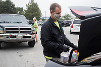 NWA Food Bank driver Jack Harrison loads food into the trunk of a car, Friday, September 11, 2020 at the Springdale Senior Center in Springdale. The senior center hosted a food drive by the Northwest Arkansas Food Bank. They handed out enough food for 310 families. The food bank distributes at the site every second Friday of the month, but they will move their mobile pantry to Parson's Arena starting October. In addition, members of the League of Women Voters also helped register people to vote and reminded them to complete the census. Check out nwaonline.com/200912Daily/ for today's photo gallery. <br /> (NWA Democrat-Gazette/Charlie Kaijo)