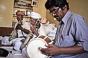75-year-old Manganiyar artist, Saqar Khan plays his Kamancha (music instrument) while his two sons, Ghewar Khan (45, Left) and Firoze Khan (38, right) accompany him during field recordings inside their house in Hamira village of Jaiselmer district in Rajasthan, India. Photo: Sanjit Das/Panos
