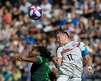 GRENOBLE, FRANCE - JUNE 22: Desire Oparanozie #9 of the Nigerian National Team, Alexandra Popp #11 of the German National Team battle for head ball during a game between Nigeria and Germany at Stade des Alpes on June 22, 2019 in Grenoble, France.