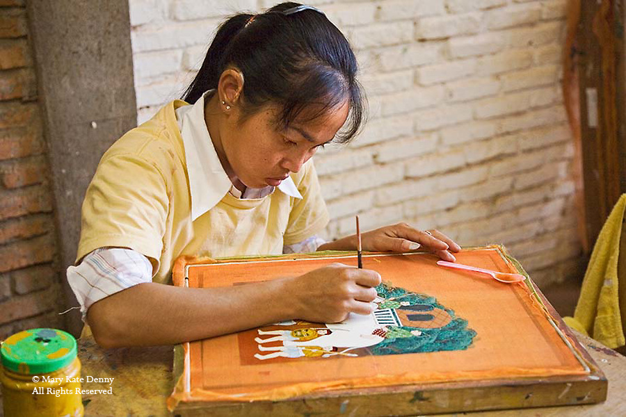 One Cambodian young female wears hearing aid and paints ancient historic scene with fine brush on silk attached to frame.