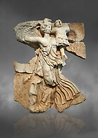 Roman Sebasteion relief  sculpture of the goddess Victory, Aphrodisias Museum, Aphrodisias, Turkey.  Against a grey background.<br /> <br /> A winged goddess Victory( Nike) flies past carrying a military trophy. She wears a long light dress and has one breast and one leg exposed. Her clothing is set in motion by her swift flight.