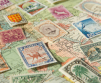 Assortment of Colorful Vintage Postage Stamps from Various Countries Around the World against a 1929 Map of the World<br />