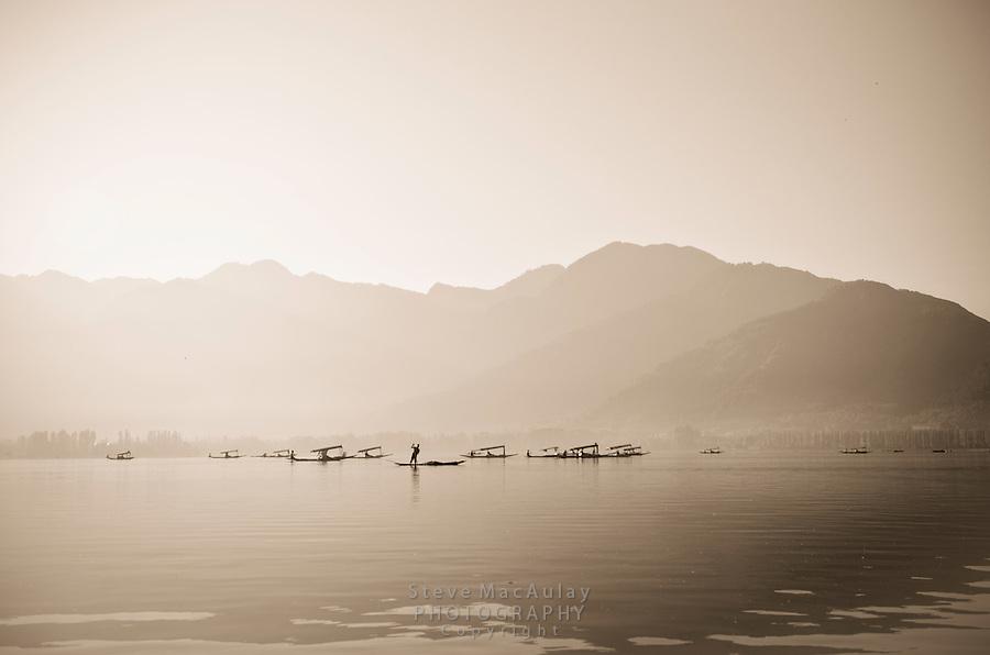 "Toned black and white photograph of traditional ""shikara"" gondolas at sunrise on the shore of Dal Lake, Srinagar, Kashmir, India."