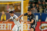 CARSON, CA - SEPTEMBER 15: Joe Corona #14 of the Los Angeles Galaxy and Roger Espinoza #17 of Sporting Kansas City battle for a loose ball during a game between Sporting Kansas City and Los Angeles Galaxy at Dignity Health Sports Complex on September 15, 2019 in Carson, California.