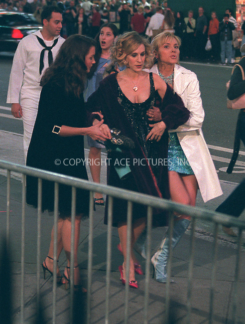 """Kristin Davis, Sarah Jessica-Parker and Kim Cattrall are filming HBO's """"Sex and the City"""" in New York's Times Square. In this scene, Sarah Jessica-Parker almost falls to the ground. It is not clear whether it happened unintentionally or in accordance with the script, but neither one is good for Sarah as she is expecting a child. May 17, 2002.  Please byline: Alecsey Boldeskul/NY Photo Press.   ..*PAY-PER-USE*      ....NY Photo Press:  ..phone (646) 267-6913;   ..e-mail: info@nyphotopress.com"""