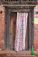 Nepal, Patan.  Curtain Partially Covering Door of House.