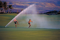 A brother and sister run through a sprinkler.