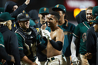 Lolo Sanchez (34) of the Greensboro Grasshoppers had his jersey ripped off by his teammates following his walk-off 2-run home run against the Hickory Crawdads at First National Bank Field on May 6, 2021 in Greensboro, North Carolina. (Brian Westerholt/Four Seam Images)