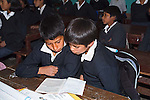 Two Peruvian elementary age males sit at desk and share book to read in school room in small town in Peru.