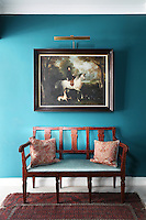 A Victorian hunting portrait hangs on the wall above an antique bench in this hallway reupholstered in Ralph Lauren fabric