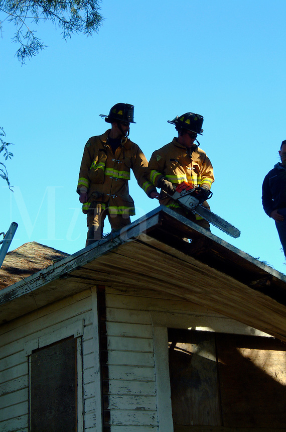 Two firefighters are silhouetted as they are about to cut a ventilation hole in the roof of a house during a house training burn for the Goldridge Fire Academy Training Class.