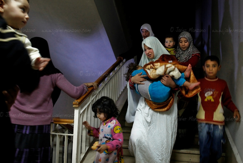 Women and children run to the basement of a building in Aleppo housing several members of the Free Syria Army (FSA) as regime tanks and helicopters attacked FSA positions nearby. .November 01, 2012...© Javier Manzano............................
