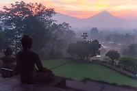 Borobudur, Java, Indonesia.  Buddha Statue and Mount Merapi at Sunrise in Morning Mist.