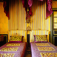 Twin beds are situated under matching canopies in a guest bedroom decorated in vividly contrasting stripes and florals