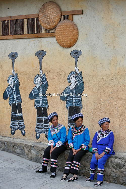 Elderly women of the ethnic Bouyei Tribe sit in front of a mural at Wangmo County in China's southwestern Guizhou Province, April 2019.