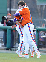 Starting pitcher Kevin Brady (19) of the Clemson Tigers hugs reliever Matt Campbell in a game against the University of Alabama-Birmingham on Feb. 17, 2012, at Doug Kingsmore Stadium in Clemson, South Carolina. UAB won 2-1. (Tom Priddy/Four Seam Images)