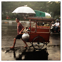 A man pulls his cart through the streets of Jakarta during a rainstorm.