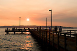 Families stroll the boardwalk and fishing pier in the community of Redondo Beach, WA.  Part of the city of Des Moines.  Sunset over the Olympic Mountains provides gorgeous late summer eveings.