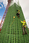 Construction workers climbing a tower of rebar.