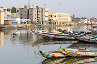 Senegal, Saint Louis.  Fishing Boats Resting on the Riverbank of the River Senegal, late afternoon.  The cream-colored building in the background is the Saint Louis hospital.