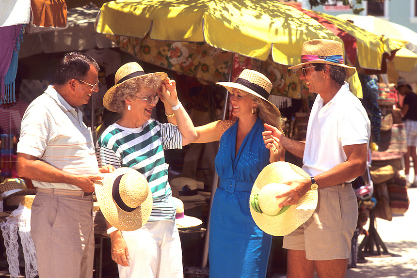 Tourist couples shopping at island straw marke