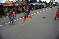 Children play football outside their makeshift home not far from Besuki village, which has been overwhelmed by mud. Since May 2006, more than 10,000 people in the Porong subdistrict of Sidoarjo have been displaced by hot mud flowing from a natural gas well that was being drilled by the oil company Lapindo Brantas. The torrent of mud - up to 125,000 cubic metres per day - continued to flow three years later.