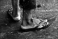 A Brazilian man, wearing the Christian cross symbol on his ankle as a protection against drowning, works in the riverport in Amazonia, Brazil, 12 April 2004. Amazonia is the world's largest dense tropical forest area. Since the 16th century the original indigenous people have been virtually pushed away or exterminated. The primal ancient unity between tribes and the jungle ambient has changed into a fight between the urban based civilization and the jungle enviroment. Although new generations of white and mestizo settlers have not become adapted to the wild tropical climate and rough conditions, they keep moving deeper into the virgin forest. The technological expansion causes that Amazonia is changing rapidly.