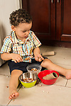 21 month old toddler boy at home playing with dried beans in bowls, using spoon and cardboard tube