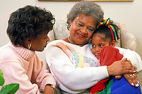 Elderly woman hugs five year old girl as mother looks on. Three generations of an African-American family. Grandmother, mother and child.