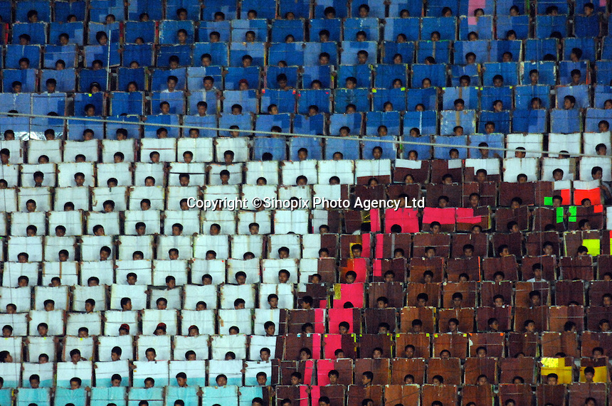 """Some of the 20,000 people who carry cards to make the huge pictures. The people have a series of pictures to make a series of huge pictures that act as a dramatic back-drop. The Arirang Games in PyongYang, North Korea. Over 100,000 perform. The Mass Games are government-organized events glorifying its two leaders of the DPRK (Democratic People's Republic of Korea) """"Dear Leader"""", Kim Jong-il and his father the """"Great Leader"""" Kim II-Sung."""