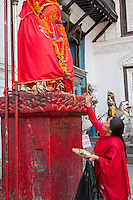 Nepal, Kathmandu.  Woman Presenting an Offering to Hanuman Statue, Durbar Square.