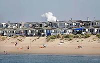 Nederland IJmuiden - 2019. Strandhuisjes in IJmuiden. Op de achtergrond een stoomwolk van Tata Steel.  Foto Berlinda van Dam / Hollandse Hoogte