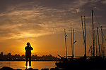Opening Day of boating along the Montlake Cut with boats lined up on Union Bay with silhouetted man taking pictures  Seattle Washington State USA.