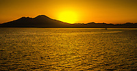 Fine Art Landscape Print Photograph. Captured along the  coastline of Greece. Spectacular red sunset scene of the ocean textures and the silhouetted mountains from the view point of the deck of a ship.