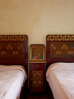A painting of Madonna and Child is flanked by twin beds with marquetry headboards