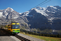 A train on the Wengernalp railway runs below the Jungfrau and mountains of the Bernese Oberland, Switzerland