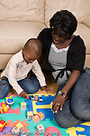 2 year old toddler boy with mother interaction playing with toys language development mother talking and involved  playing with small plastic human figures African American vertical