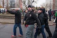 """Ca. 550 Neonazis, Hooligans, NPD-Mitglieder und Mitglieder der Neonazipartei """"Die Rechte"""", sowie eine sog. Buergerinitiative """"Gegen Asylmissbrauch den Mund aufmachen"""" protestierten am Samstag den 22. November 2014 gegen ein Fluechtlingsheim in Berlin Marzahn-Hellersdorf gegen eine geplante Unterkunft fuer Fluechtlinge.<br /> Dagegen protestieren bereits Stunden vor dem Aufmarsch ueber 3.500 Menschen an mehreren Punkten der Marschroute. Die Polizei lies sie zunaechst gewaehren.<br /> Bis zum Einbruch der Dunkelheit konnte der rechtsradikale Aufmarsch nur ca. 70 Meter Wegstrecke zurueck legen und wurde dann von der Polizei in einer chaotischen Aktion zum S-Bahnhof gebracht. Gegendemonstranten gelang es nach unverstaendlichen Polizeimanoevern bis auf wenige Meter an die Rechtsradikalen zu gelangen und es kam zu Auseinandersetzungen bei denen beide Seiten sich mit Flaschen, Steinen und Feuerwerkskoerpern beworfen.<br /> Im Bild: Neonazi-Hooligans werden von der Polizei zum Sammelplatz ihres Aufmarsches geleitet und poebeln umstehende Journalisten an.<br /> Der Hooligan in der Bildmitte traegt Quartzhandschuhe, die bei Schlaegen besonders schwere Verletzungen verursachen koennen.<br /> 22.11.2014, Berlin<br /> Copyright: Christian-Ditsch.de<br /> [Inhaltsveraendernde Manipulation des Fotos nur nach ausdruecklicher Genehmigung des Fotografen. Vereinbarungen ueber Abtretung von Persoenlichkeitsrechten/Model Release der abgebildeten Person/Personen liegen nicht vor. NO MODEL RELEASE! Nur fuer Redaktionelle Zwecke. Don't publish without copyright Christian-Ditsch.de, Veroeffentlichung nur mit Fotografennennung, sowie gegen Honorar, MwSt. und Beleg. Konto: I N G - D i B a, IBAN DE58500105175400192269, BIC INGDDEFFXXX, Kontakt: post@christian-ditsch.de<br /> Bei der Bearbeitung der Dateiinformationen darf die Urheberkennzeichnung in den EXIF- und  IPTC-Daten nicht entfernt werden, diese sind in digitalen Medien nach §95c UrhG rechtlich geschuetzt. Der Urhebervermerk wird gemae"""