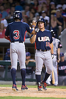 Buddy Reed (3) of the US Collegiate National Team is greeted at home plate by teammate Matt Thaiss (19) as he scores a run against the Cuban National Team at BB&T BallPark on July 4, 2015 in Charlotte, North Carolina.  The United State Collegiate National Team defeated the Cuban National Team 11-1.  (Brian Westerholt/Four Seam Images)