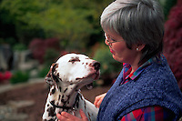 Middle-aged woman and her dalmatian gaze at each other.