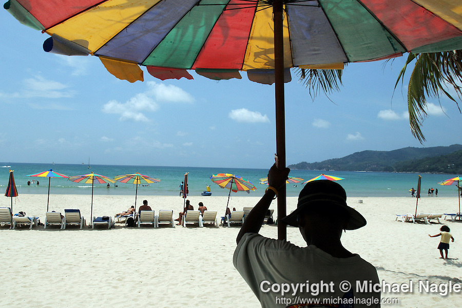 PHUKET  --  MARCH  26, 2005:  A man sets up sun umbrellas for tourists on March 26, 2005 in Phuket, Thailand.  Three months after the tsunami that devastated the region, Phuket is ready and waiting for tourists to start coming back to it's beaches and resorts.  People hang out on Patong Beach.  (PHOTOGRAPH BY MICHAEL NAGLE)
