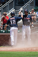 First baseman Matt Snyder #33 of the Ole Miss Rebels greets teammate Tanner Mathis #12 after he scored during the NCAA Regional baseball game against the Texas Christian University Horned Frogs on June 1, 2012 at Blue Bell Park in College Station, Texas. Ole Miss defeated TCU 6-2. (Andrew Woolley/Four Seam Images).