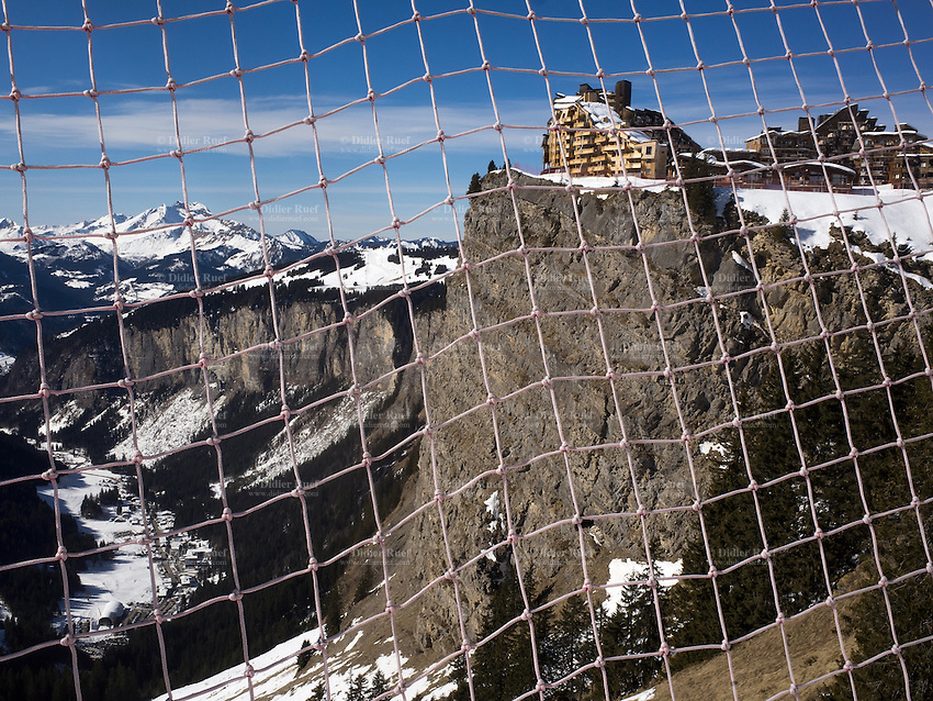"""France. Haute-Savoie department. Avoriaz. View through the safety nets on the mountain resort and the french Alps. Avoriaz is built on a book high above the town of Morzine (down in the valley). Avoriaz is one of the major French ski destinations catering for all standards of skiing and ranks among the top snowboarding destinations. Cars are forbidden in the mountain resort. Avoriaz is part of the """"Portes du Soleil"""", an alpine ski resorts and a major skisports destination between the swiss and french Alps, encompassing thirteen resorts with more than 650 km of marked pistes and about 200 lifts in total, spread over 14 valleys and 1036 square km. 20.02.2015 © 2015 Didier Ruef"""