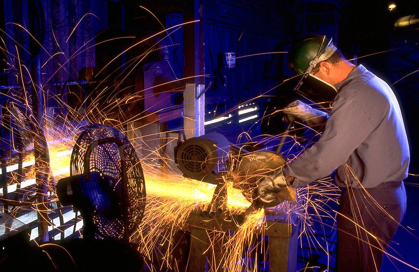 A steel worker tests material on a bench grinder. Texas.