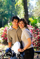 Hispanic couple attractive with helmets done with riding bikes outdoors.